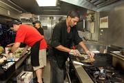 Jason Storms, Tammy Young, owner and Ronald Rodriguez cooking for customers inside Rollin' Zoinks.