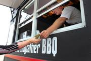 Mark Gabrick, owner of The Hogfather, Kansas City barbeque food truck, serves lunch to customers from Parallon and Honeywell in Largo.