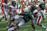 Charlotte 49ers running back Alan Barnwell takes on two defenders. The 49ers beat the Campbell Fighting Camels 52-7 in their inaugural football game at Jerry Richardson Stadium, on Aug. 31, 2013.