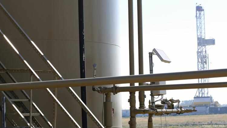 A Drilling Rig Is Seen Looming Behind An Oil Storage Tank In The Oilfields  Of The