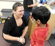 Recovering from cancer treatment, with her hair just growing back, preschool teacher Aubrei McGinn talks with student Mahin Mohammad, 4, on the first day of the new school year in September 2013.